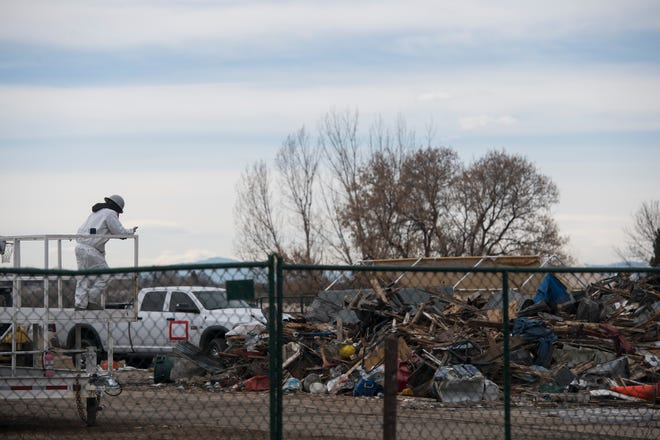 A crews member in a hazardous material suit waits near a pile of debris as others work to demolish a house and garage deemed to be posing a public safety threat to the surrounding neighborhood due in part to hazardous levels of methamphetamines on Wednesday, Feb. 13, 2019, in Loveland, Colo.