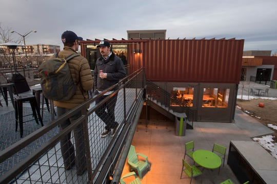 New Belgium Brewing employees Dave Glor, left, and Cody Reif sample wine on the patio on Tuesday, Feb. 12, 2019, during a soft opening at The Infinite Monkey Theorem in Fort Collins, Colo.