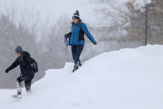 Students walk across a snow pile on the University of Wisconsin-Green Bay campus on Feb. 13 in Green Bay.