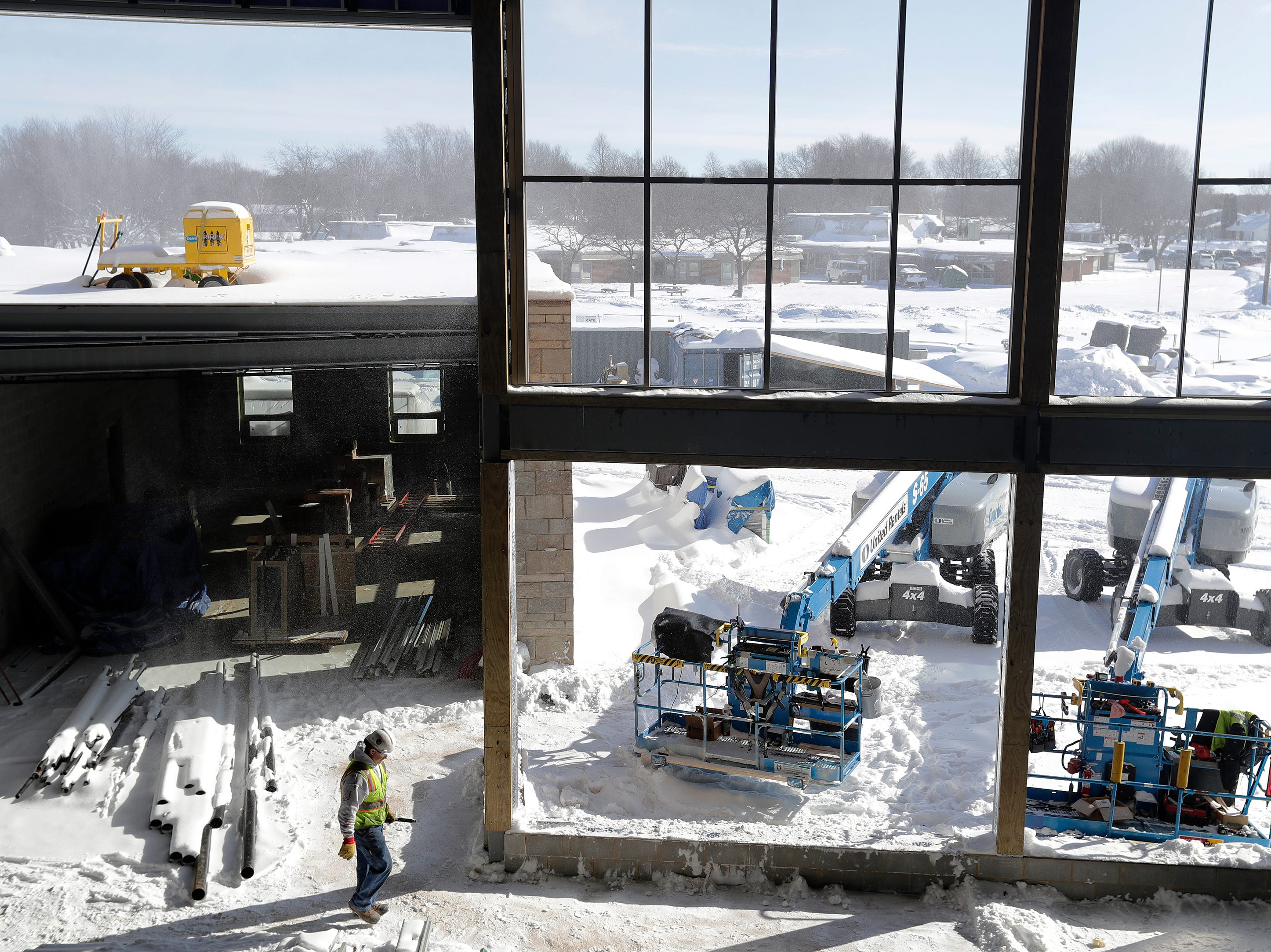 A construction worker walks through the  cafeteria area of the new Baird Elementary School  in Green Bay on Wednesday. The existing Baird Elementary is visible in the background. The new school is scheduled to open in fall.