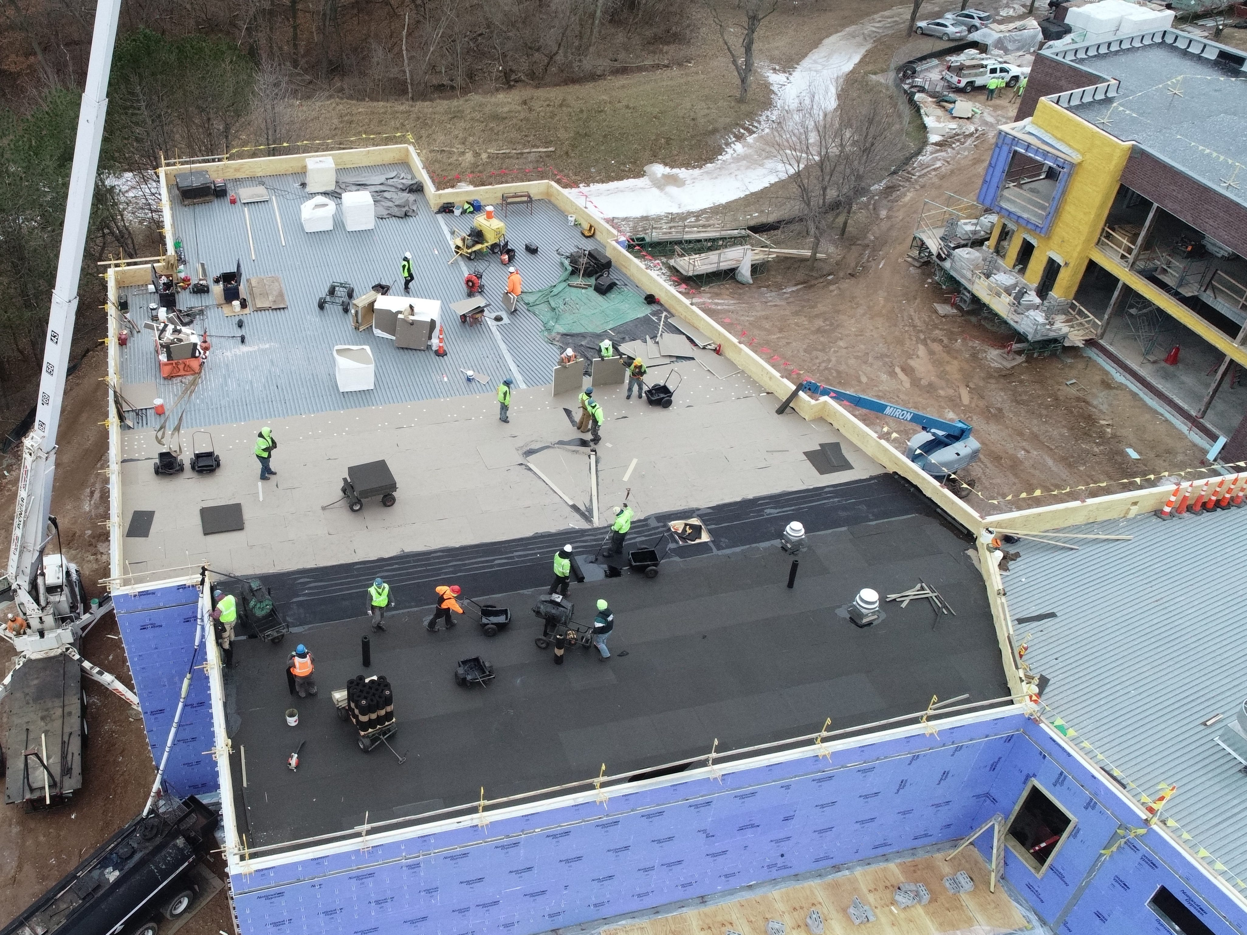 An aerial view of work on the roof of the under-construction Baird Elementary School.