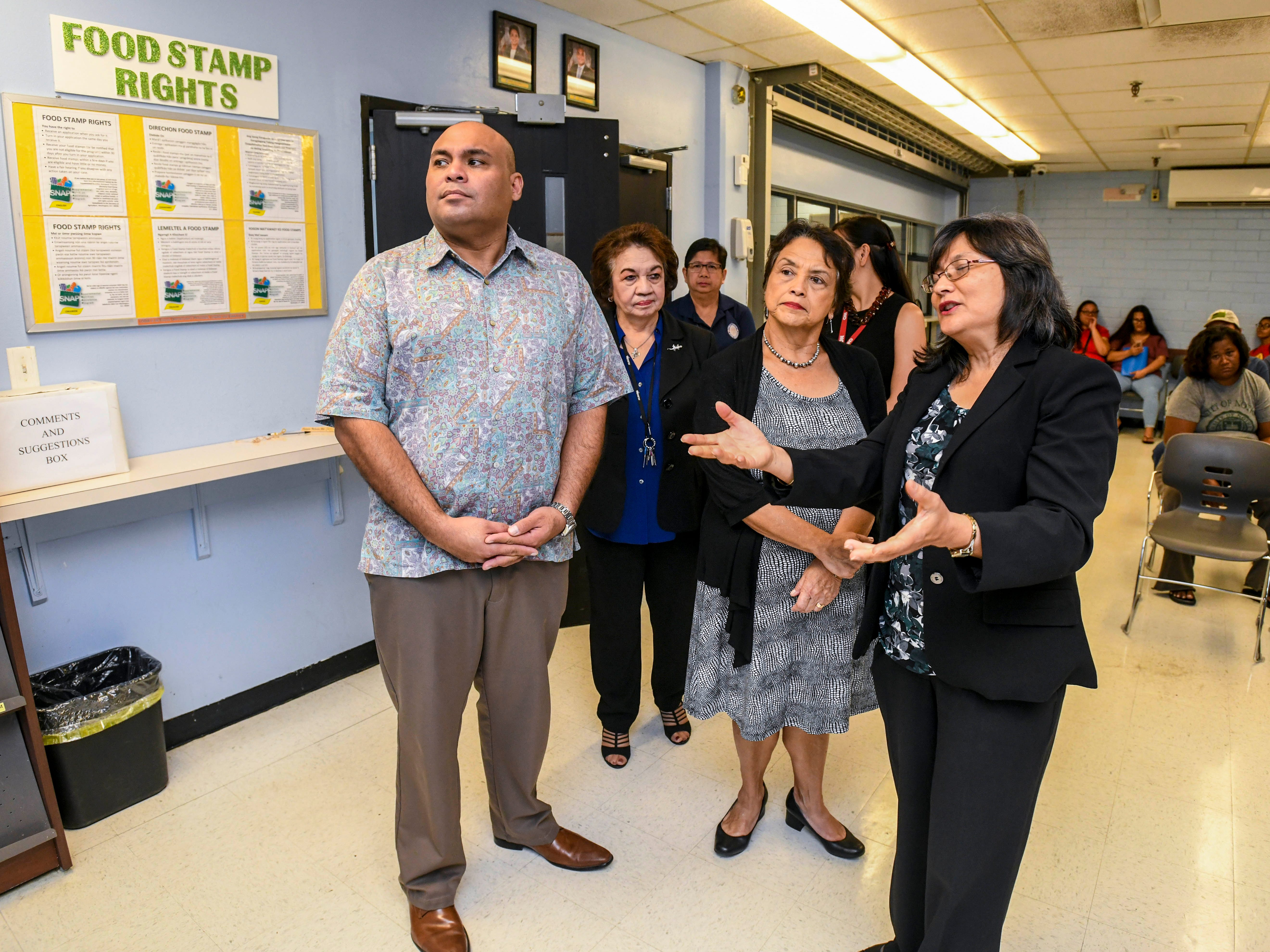 Acting Director Linda Unpingco DeNorcey, front right, explains the services provided by the Bureau of Economic Security SNAP/Public Assistance Division to Gov. Lou Leon Guerrero and Lt. Gov. Josh Tenorio during a walk-through tour of the Department of Public Health and Social Services in Mangilao on Wednesday, Feb. 13, 2019.