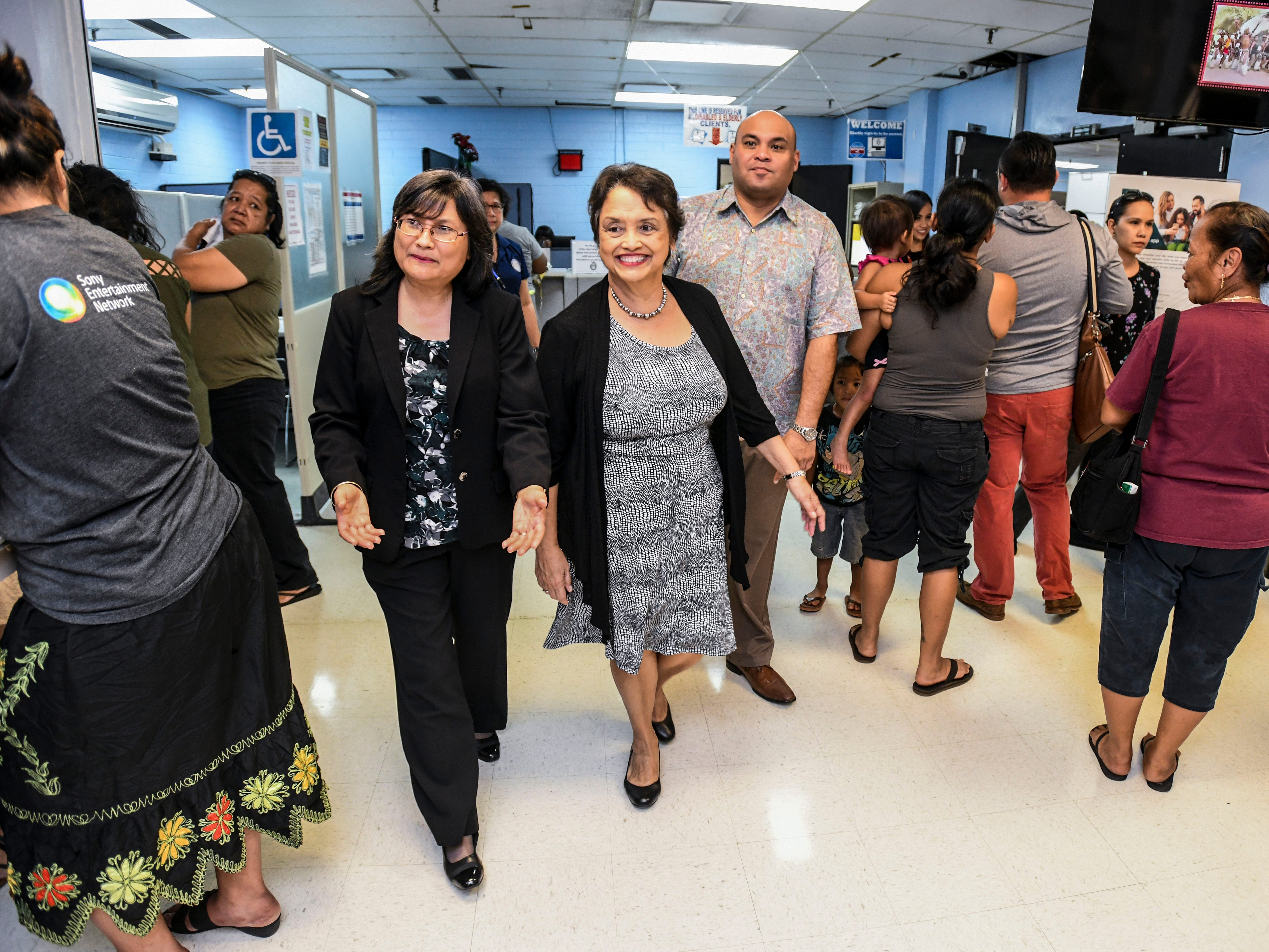 Gov. Lou Leon Guerrero, center, and Lt. Gov. Josh Tenorio, walk through residents seeking assistance within the Bureau of Economic Security SNAP/Public Assistance Division as they are lead on a tour of the Department of Public Health and Social Services by Acting Director Linda Unpingco DeNorcey on Wednesday, Feb. 13, 2019.