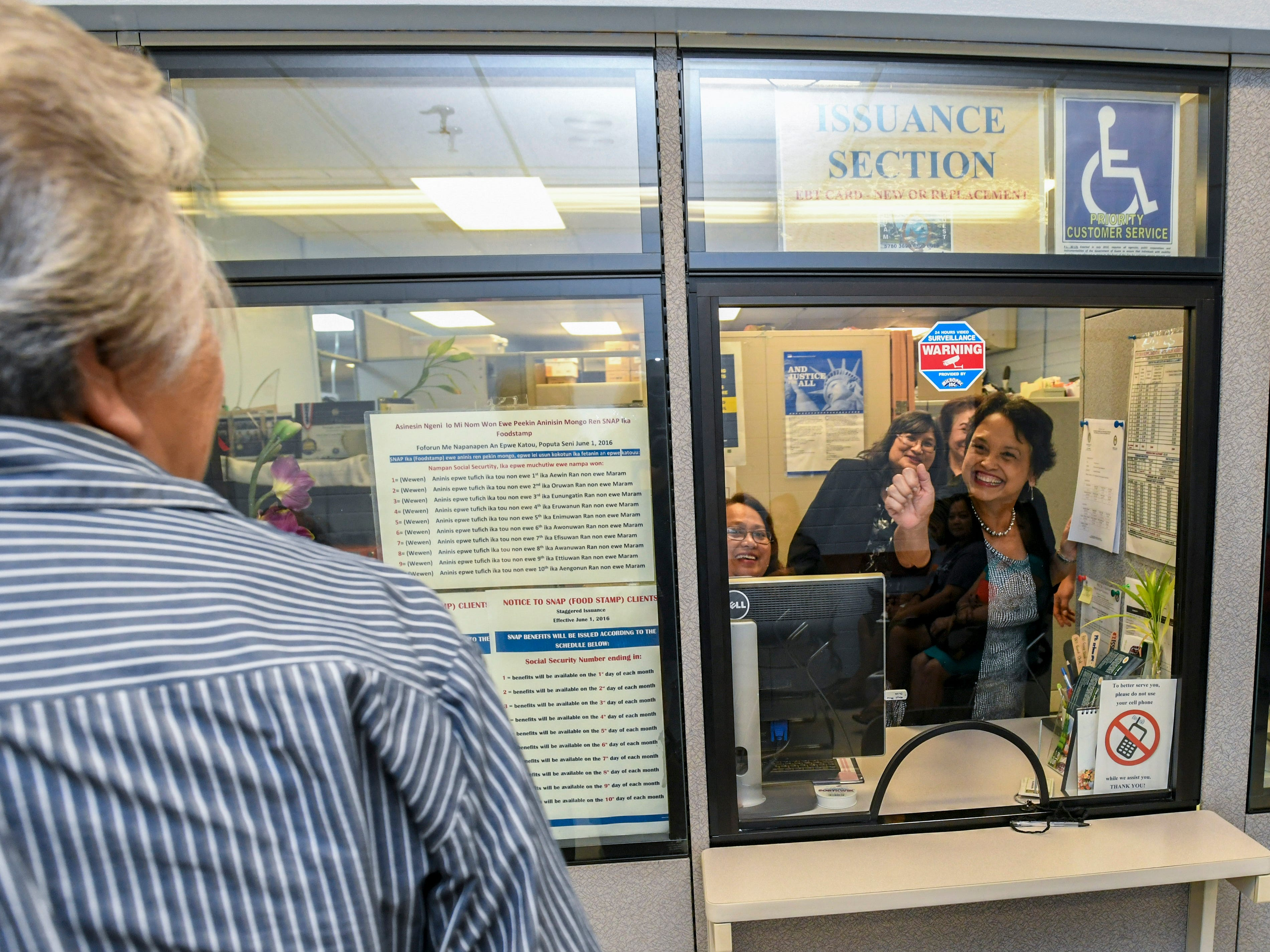 Gov. Lou Leon Guerrero waves to a woman through a glass partition window at the Bureau of Economic Security SNAP/Public Assistance Division at the Department of Public Health and Social Services in Mangilao on Wednesday, Feb. 13, 2019. The governor and Lt. Gov. Josh Tenorio were greeted by the agency's leadership, toured the healthcare facility and met with staff members and other stakeholders.