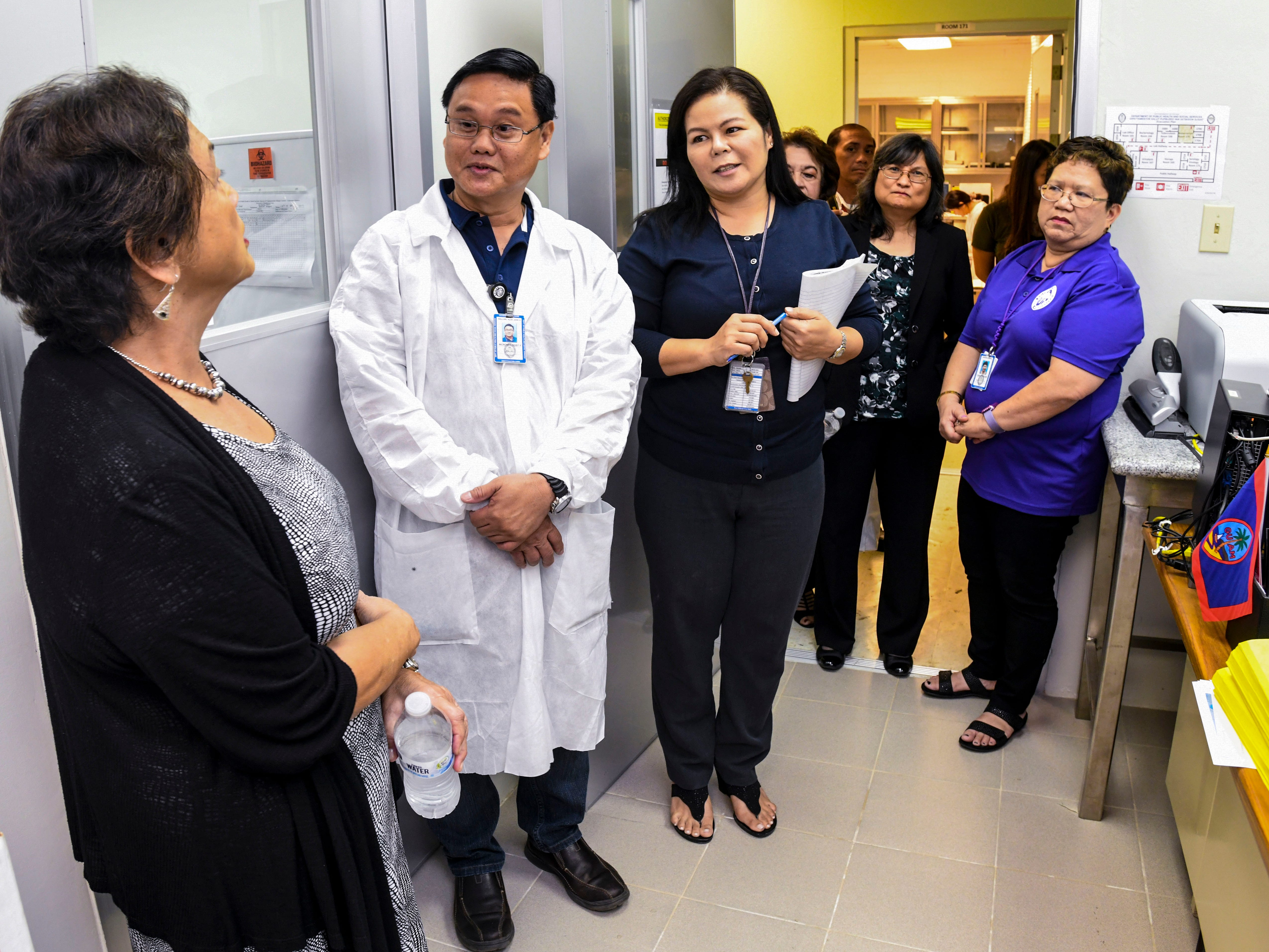 Gov. Lou Leon Guerrero, left, chats with Microbiologist Alan John Malari and other stakeholders during a tour of the Department of Public Health and Social Services in Mangilao on Wednesday, Feb. 13, 2019.