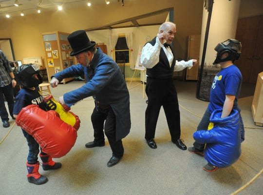Madison Burnett, 8, left, and Nolan Burnett, 11, both of Indianapolis, get some lessons in boxing from presidents Martin Van Buren, left, portrayed by Mike Schoening of Noblesville, and Andrew Jackson, portrayed by  Dwight Gallian of Carmel, iduuring the Presidents Day celebration at Conner Prairie Interactive History Park on Feb. 17, 2014.