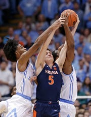 Virginia's Kyle Guy (5) battles North Carolina's Coby White and Kenny Williams, right, for the ball during a game in Chapel Hill, N.C.,  on Tuesday. Virginia won 69-61. (AP Photo/Gerry Broome)