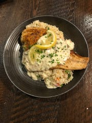 Redfish is served with made-to-order rice pilaf, topped with bacon and andouille cream sauce, at Genna Benna's.