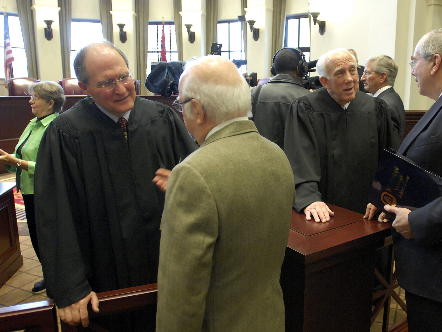 Bill Waller Jr., (left) and Jim Kitchens of Crystal Springs speak with well wishers following a swearing in ceremony for new justices ceremony in the new Gartin Justice Building in Jackson.