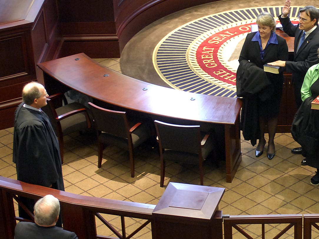 Bill Waller Jr., (left) swears in new justices.