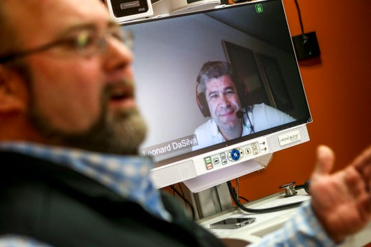Dr. Leonard DaSilva watches through a camera as Michael Cupples, left, presents about the telemedicine machines being used at Baptist Memorial Hospital in Huntingdon.