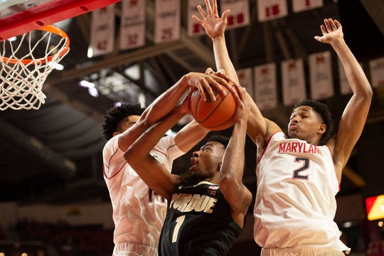 Terrapins forward Ricky Lindo Jr. (14) and  guard Aaron Wiggins (2) defend Purdue Boilermakers forward Aaron Wheeler (1) shot during the first half at XFINITY Center.