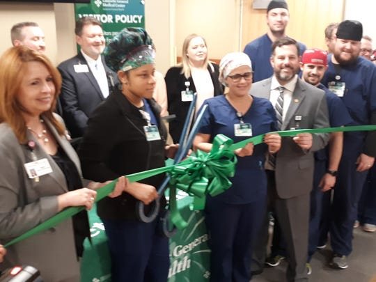 Employees gather in Lafayette General Medical Center's newly renovated catherization labs cut a ceremonial ribbon to formally open the facility.