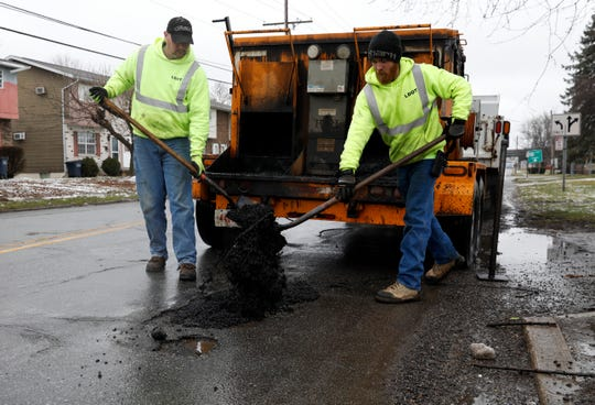 Lancaster Department of Transportation employees Mike Streets, left, and Josh Williamson fill a pothole Monday, Feb. 11, 2019, on South Broad Street in Lancaster.