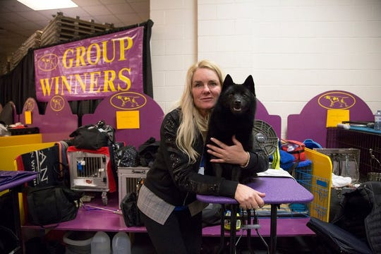 Colton, a schipperke, poses with his handler Christa Cook backstage at Madison Square Garden during the Westminster Kennel Club Dog Show in New York, Tuesday, Feb. 12, 2019. A day after winning the nonsporting group and a place in the final ring of seven, Colton was ruled ineligible for best in show.