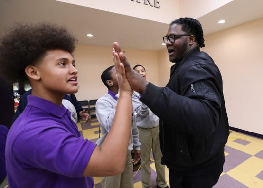 West End School student Jasiah Baylor, left, compared hand size with former U of L football player Jamon Brown.  Brown, who is in the NFL now, visited the school to speak to the students about ways to prevent bullying.  He plays right guard for the New York Giants.Feb. 11, 2019