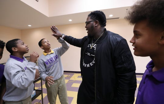 West End School student Omari Goodwin, second from left, compared hand size with former U of L football player Jamon Brown.  Brown, who is in the NFL now, visited the school to speak to the students about ways to prevent bullying.  He plays right guard for the New York Giants.Feb. 11, 2019
