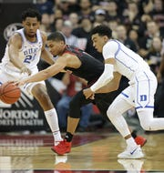 Louisville's Cunningham nearly loses the ball against Duke defenders. Feb. 12, 2019
