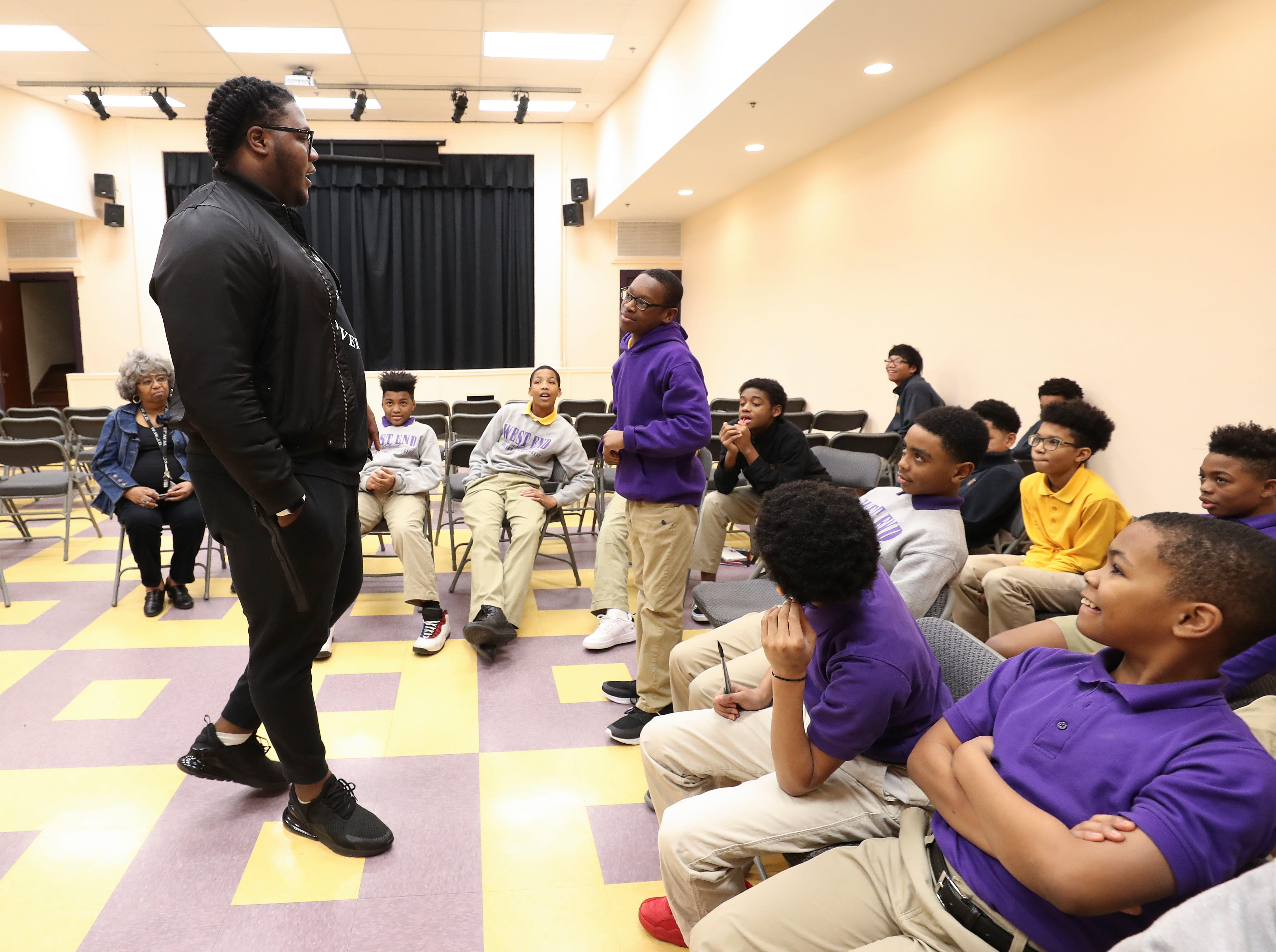 Jamon Brown, left, a former U of L football player who is in the NFL now, spoke to a group of students at the West End School about ways to prevent bullying.  He plays right guard for the New York Giants.Feb. 11, 2019