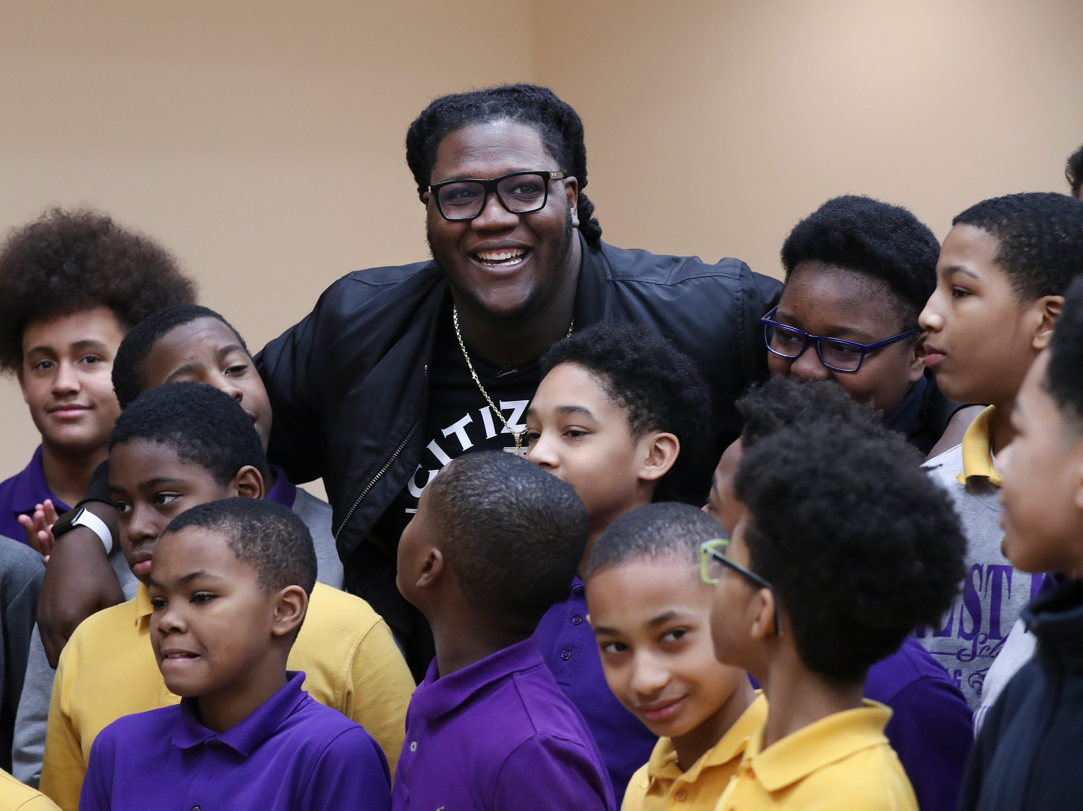 Jamon Brown, center, a former U of L football player who is in the NFL now, embraced a group of students at the West End School.  Brown spoke to the students about ways to prevent bullying.  He plays right guard for the New York Giants.Feb. 11, 2019