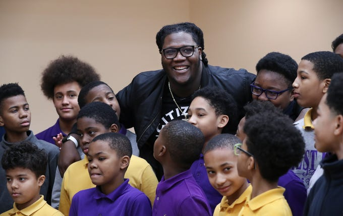 Jamon Brown, center, a former U of L football player who is in the NFL now, embraced a group of students at the West End School.  Brown spoke to the students about ways to prevent bullying.  He plays right guard for the New York Giants.