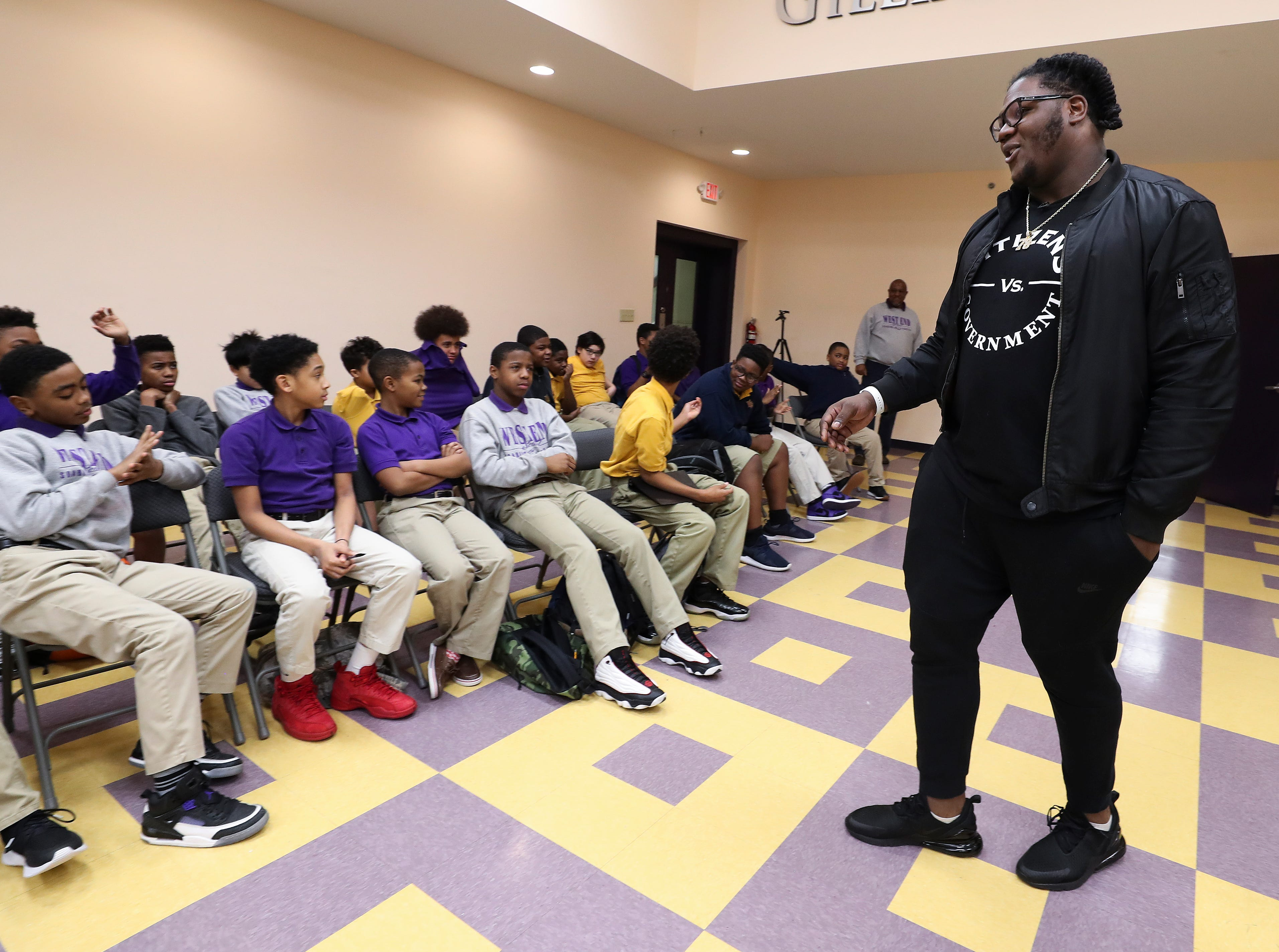 Jamon Brown, right, a former U of L football player who is in the NFL now, spoke to a group of students at the West End School about ways to prevent bullying.  He plays right guard for the New York Giants.Feb. 11, 2019