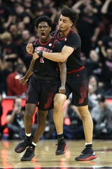 Louisville's Jordan Nwora grabs teammate Darius Perry from behind in celebration after Perry tipped in a shot as the clock ran down before halftime. Feb. 12, 2019