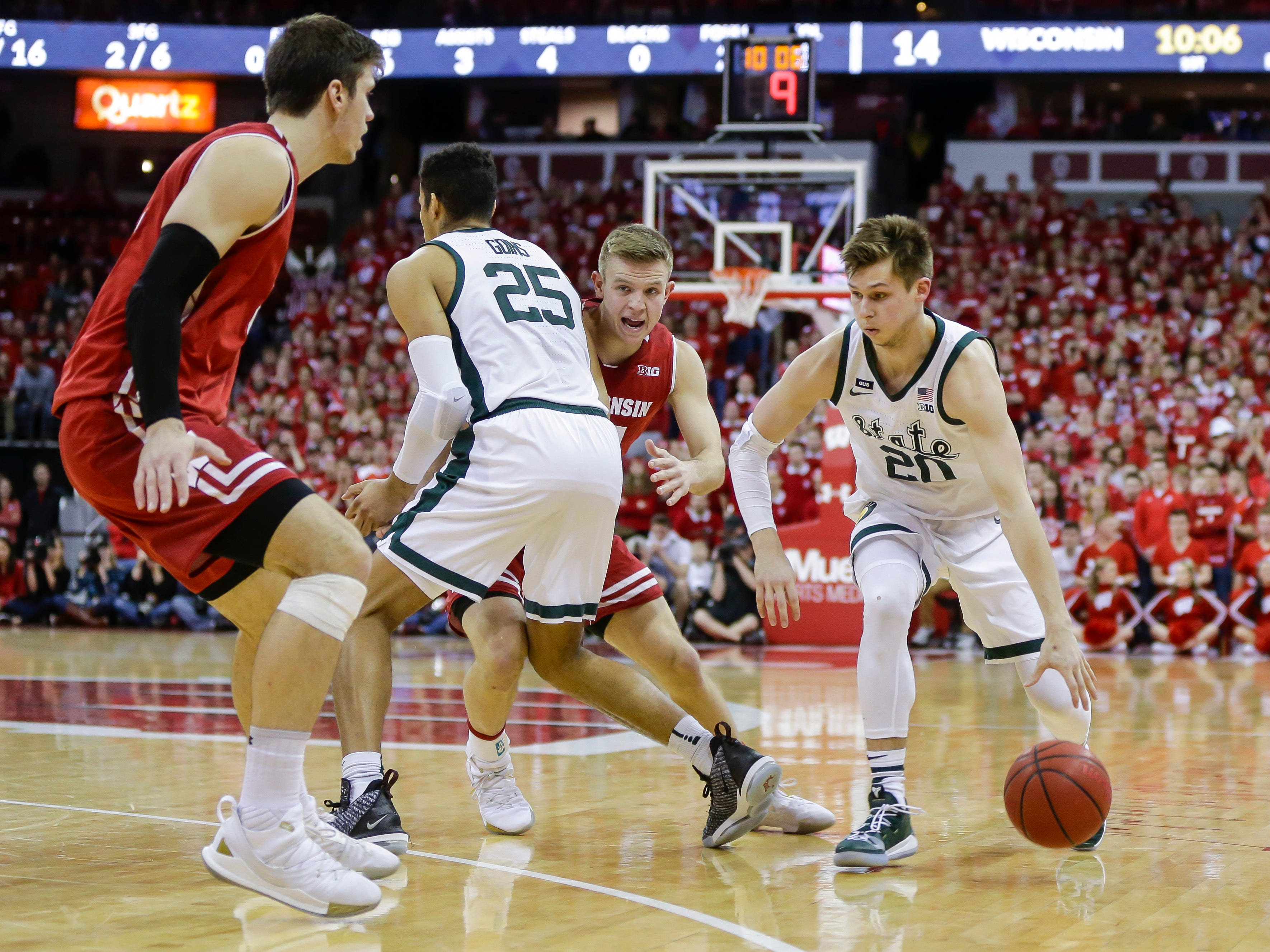 Michigan States's Matt McQuaid (20) drives against Wisconsin's Ethan Happ, left, and Brad Davison during the first half of an NCAA college basketball game Tuesday, Feb. 12, 2019, in Madison, Wis.