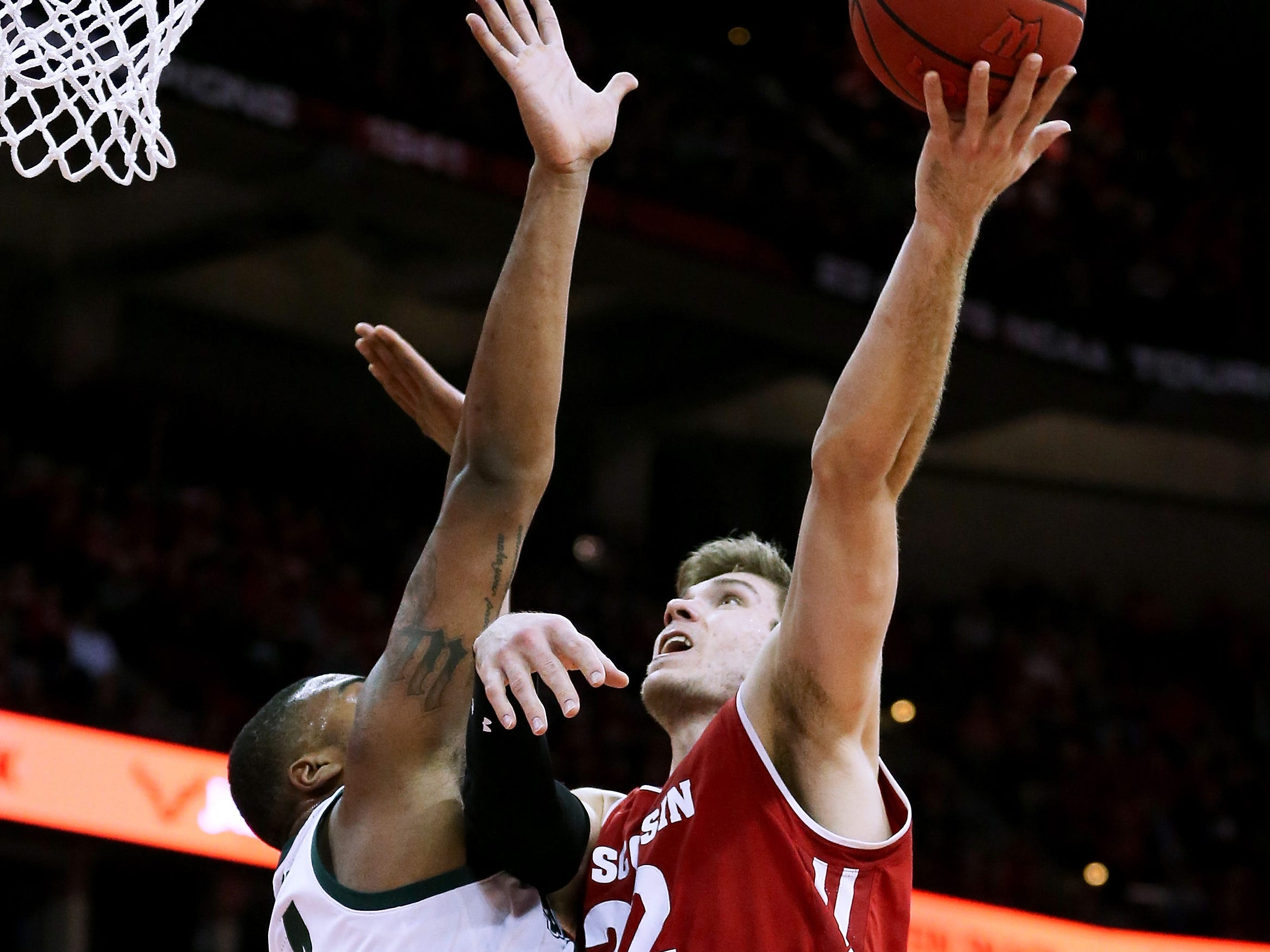 Ethan Happ #22 of the Wisconsin Badgers attempts a shot while being guarded by Nick Ward #44 of the Michigan State Spartans in the first half at the Kohl Center on February 12, 2019 in Madison, Wisconsin.