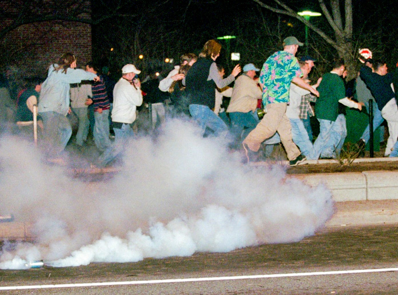 People flee from tear gas along Grand River Avenue in East Lansing, Michigan, early Sunday morning on March 28, 1999, following the Michigan State loss to Duke at the NCAA Final Four of the Men's Basketball Tournament in St. Petersburg, Fla.
