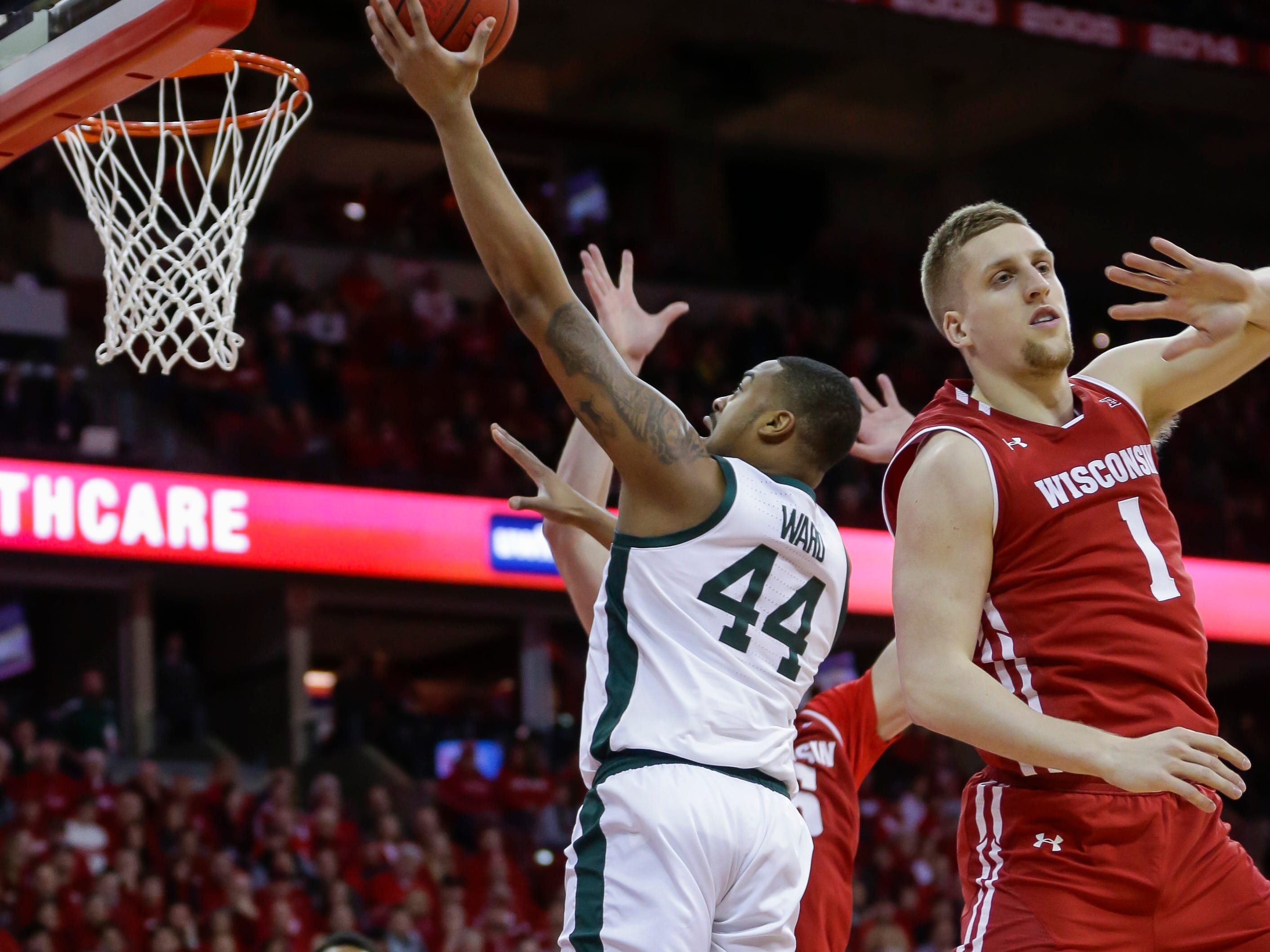 Michigan States's Nick Ward (44) shoots past Wisconsin's Brevin Pritzl (1) and Nate Reuvers, behind, during the first half of an NCAA college basketball game Tuesday, Feb. 12, 2019, in Madison, Wis.