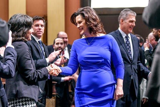 Michigan Gov. Gretchen Whitmer shakes hands with guests as she enters the House chamber before delivering her State of the State address on Tuesday, Feb. 12, 2019, at the Michigan State Capitol in Lansing.