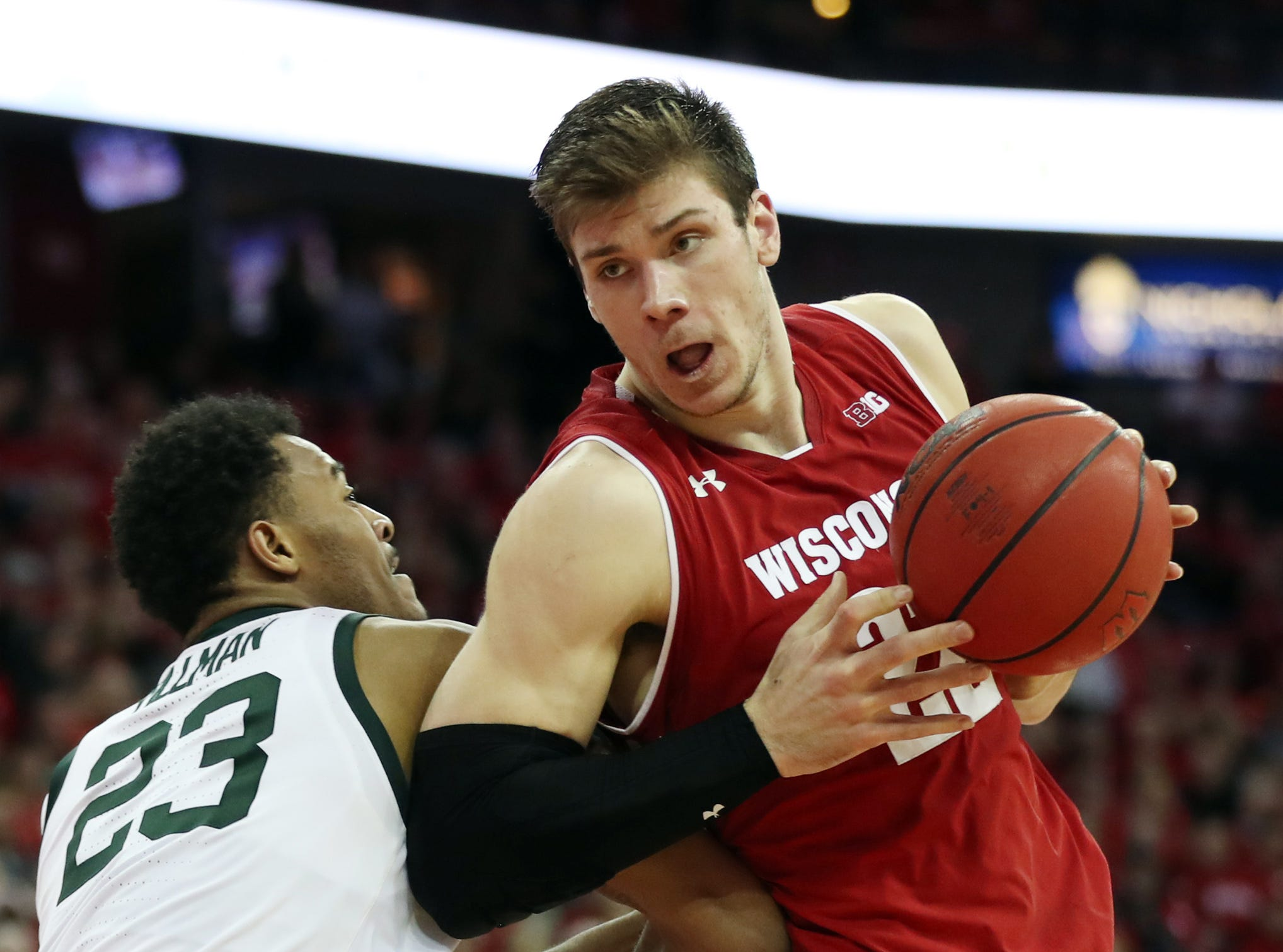 Wisconsin Badgers forward Ethan Happ (22) controls the ball as Michigan State Spartans forward Xavier Tillman (23) defends during the second half at the Kohl Center.