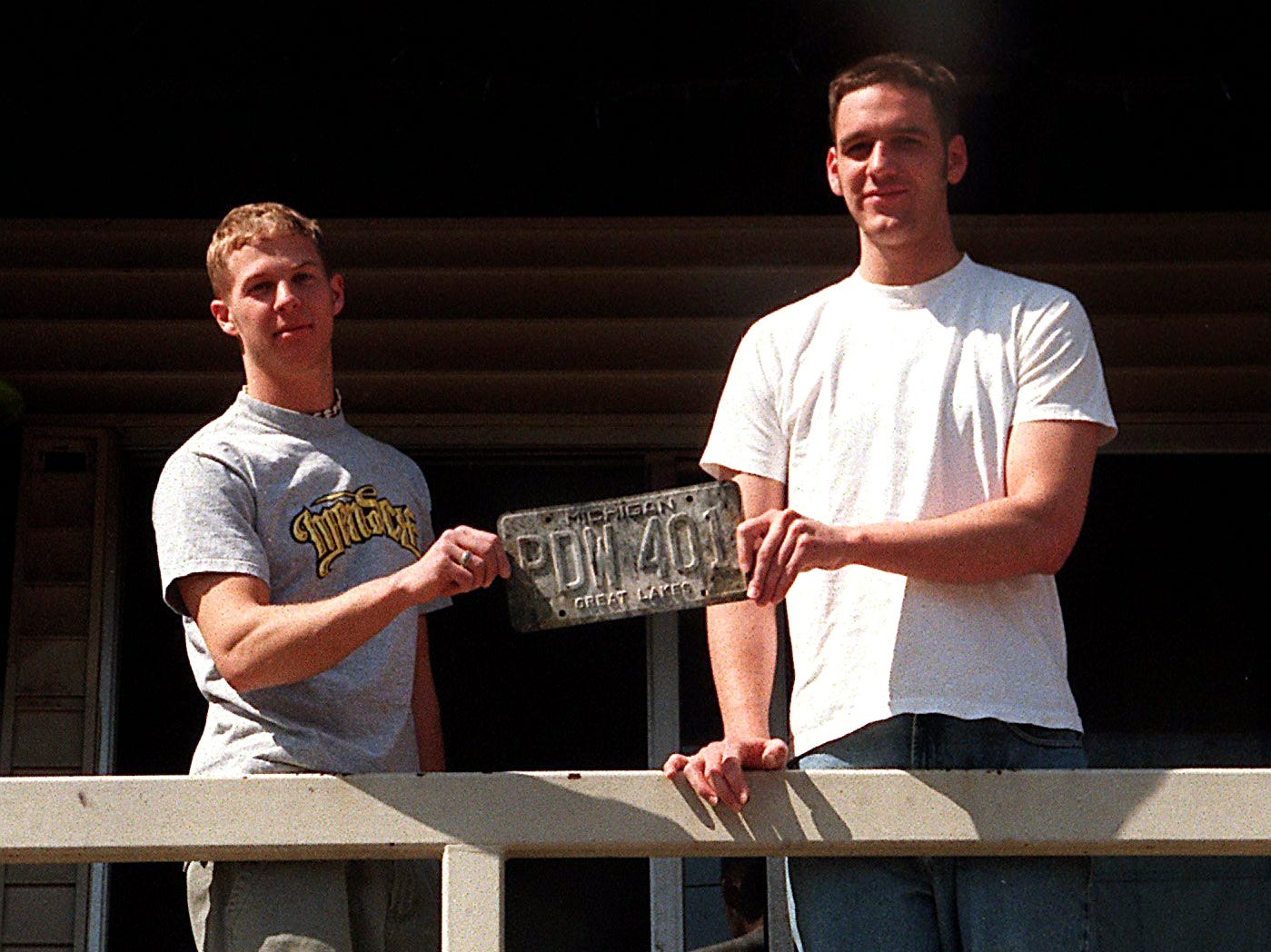 Cedar Village residents Jeremy Dunn, left, and Clint Cherney hold up a charred license plate on Sunday, March 28, 1999, in East Lansing. They recovered it from the site of one of the many bonfires around Cedar Village the night before.