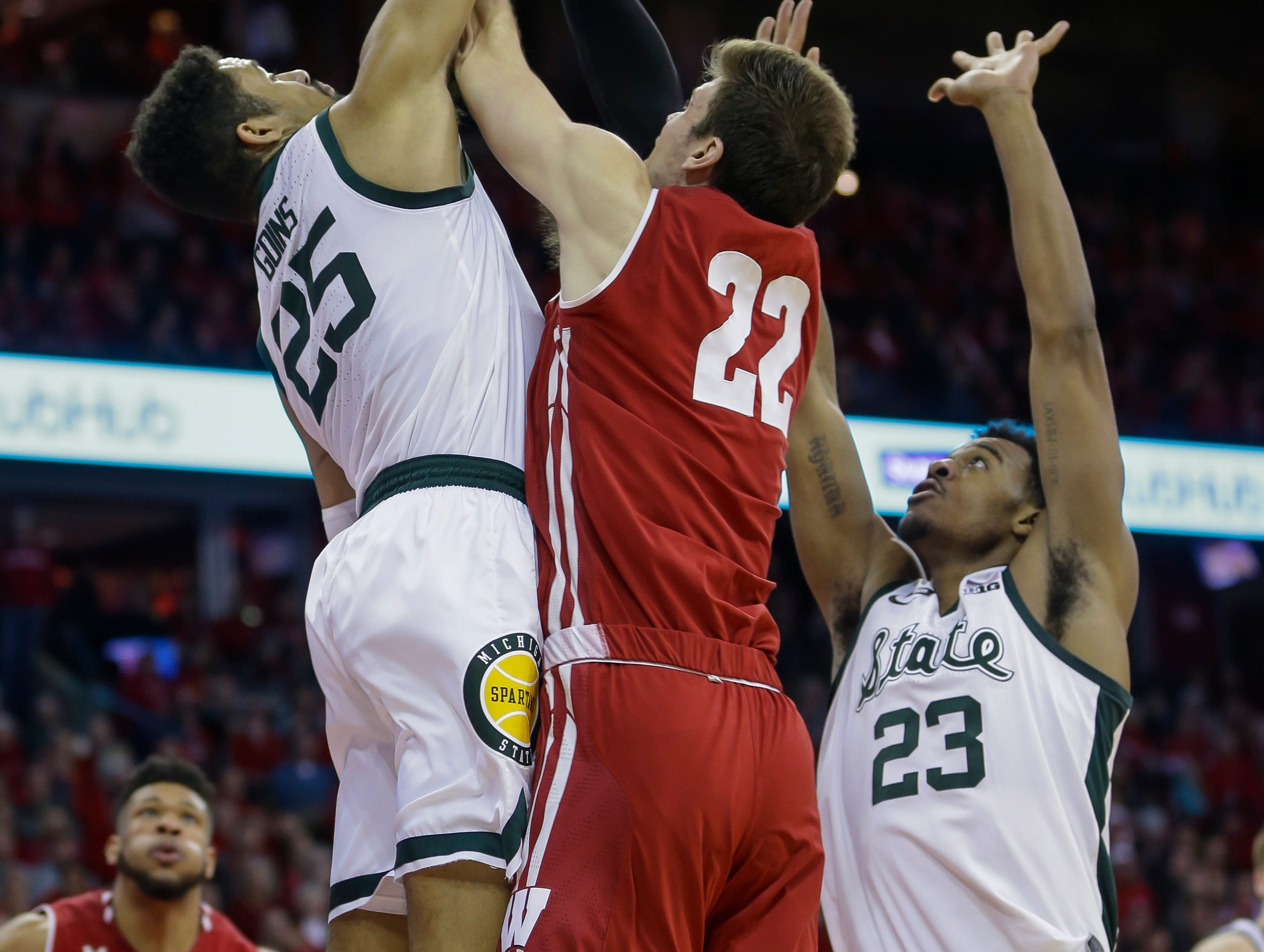 Michigan States's Kenny Goins (25) blocks a shot by Wisconsin's Ethan Happ (22) during the second half of an NCAA college basketball game Tuesday, Feb. 12, 2019, in Madison, Wis. At right is Michigan States's Xavier Tillman.