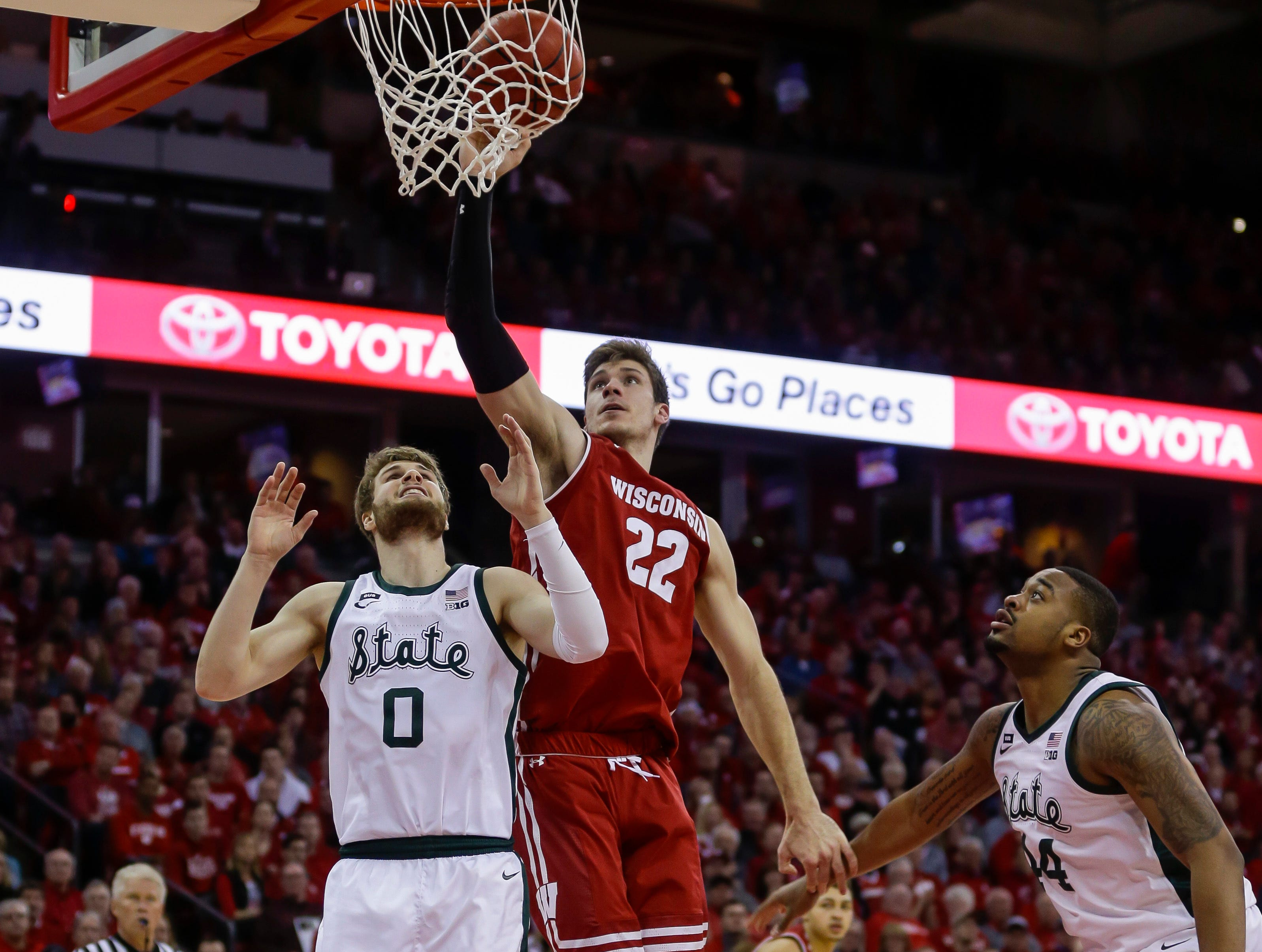 Wisconsin's Ethan Happ (22) shoots against Michigan States's Kyle Ahrens (0) and Nick Ward, right, during the second half of an NCAA college basketball game Tuesday, Feb. 12, 2019, in Madison, Wis. Michigan State won 67-59.