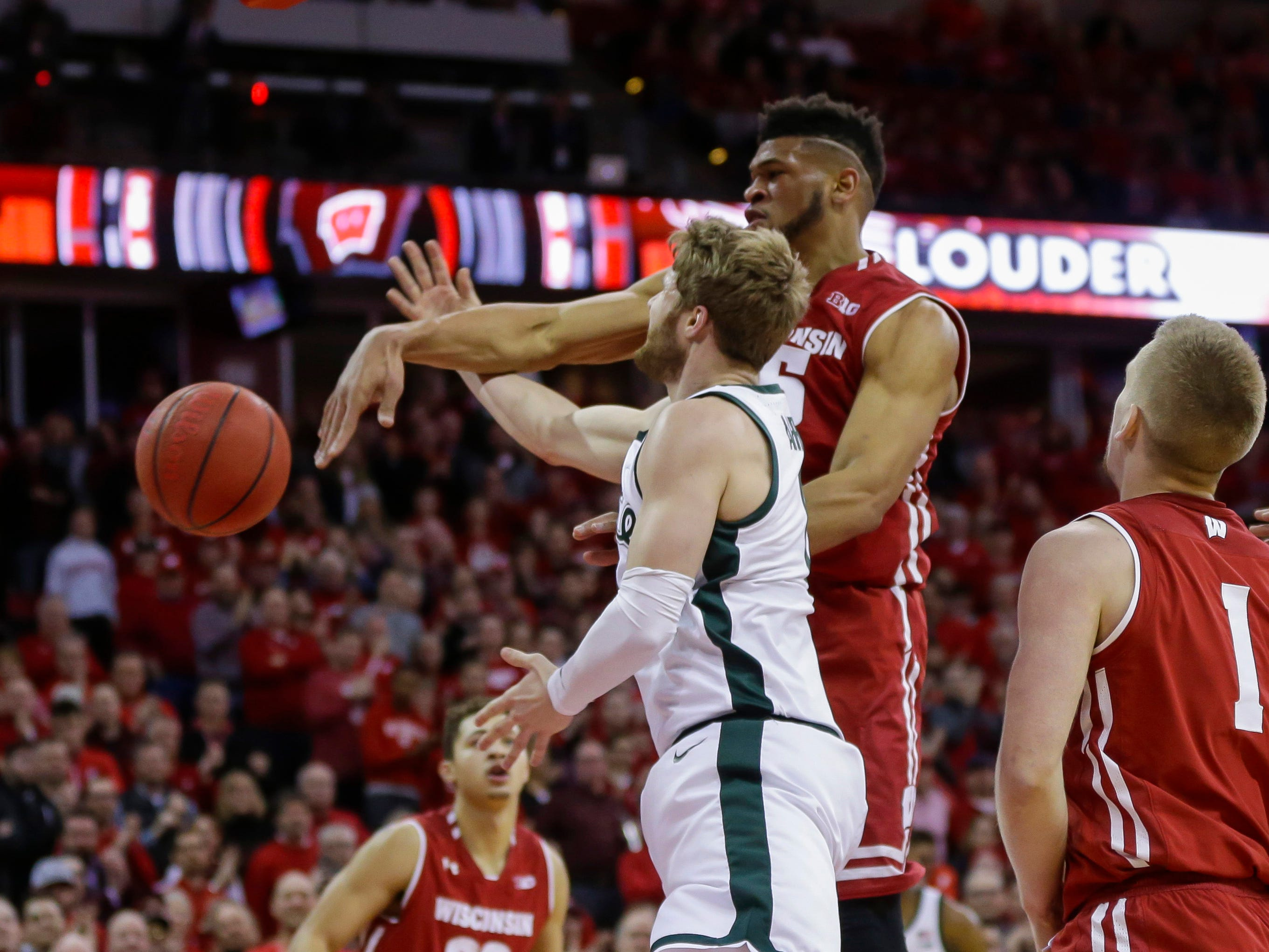 Wisconsin's Charles Thomas (15) blocks a a shot by Michigan States's Kyle Ahrens (0) during the first half of an NCAA college basketball game Tuesday, Feb. 12, 2019, in Madison, Wis.