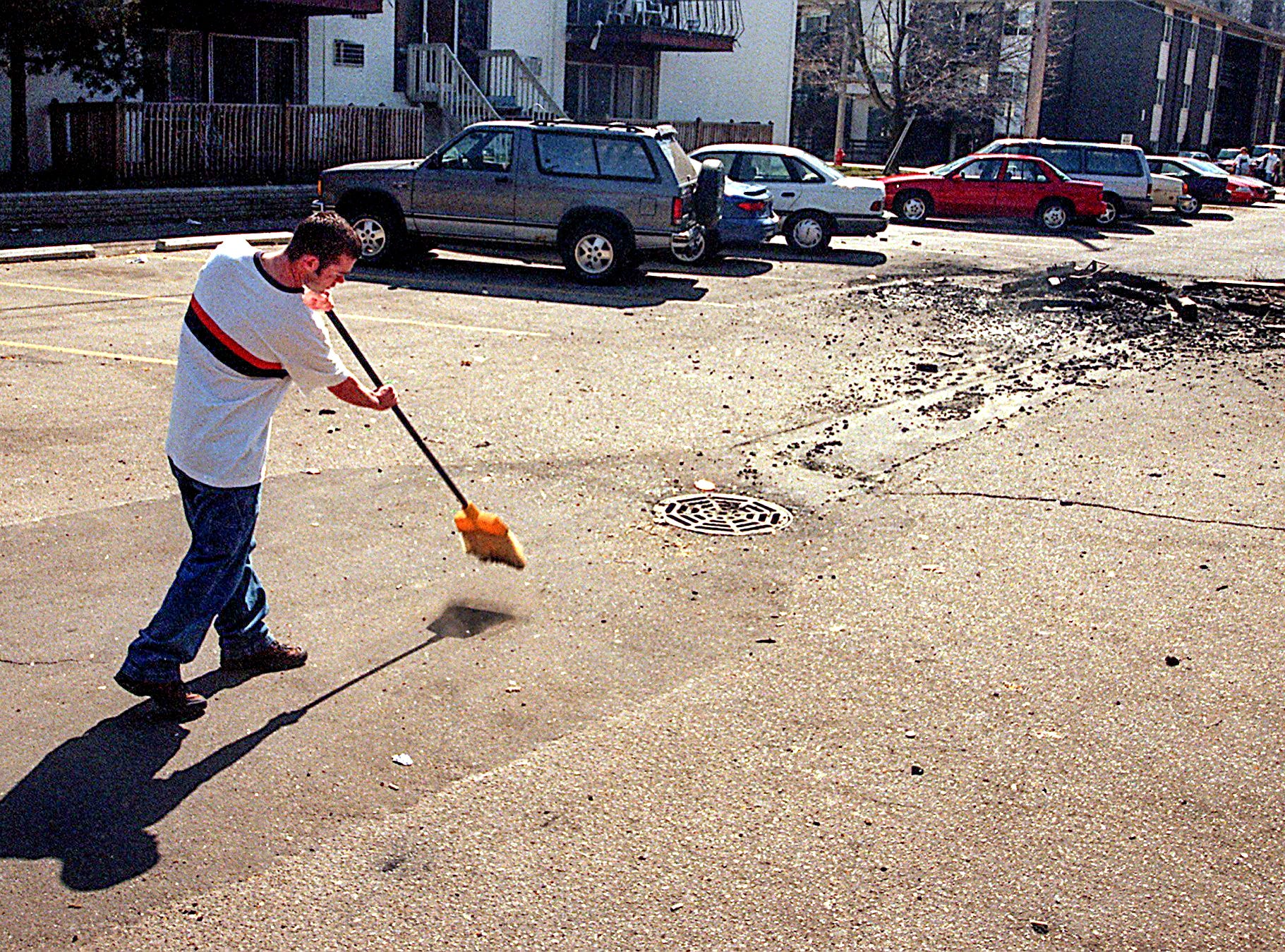 Chris Hopper, a resident of Cedar Village, sweeps up broken beer bottles outside his apartment Sunday, March 28, 1999, the morning after  riot in East Lansing.
