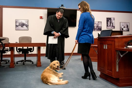 Ingham County Circuit Court Chief Judge Richard Garcia, left, swears in new courtroom support dog Kory as the dog's handler Jessica Carls, a victim rights specialist at the Ingham County ProsecutorÕs Office, looks on at the Veteran's Memorial Courthouse on Wednesday, Feb. 13, 2019, in Lansing.