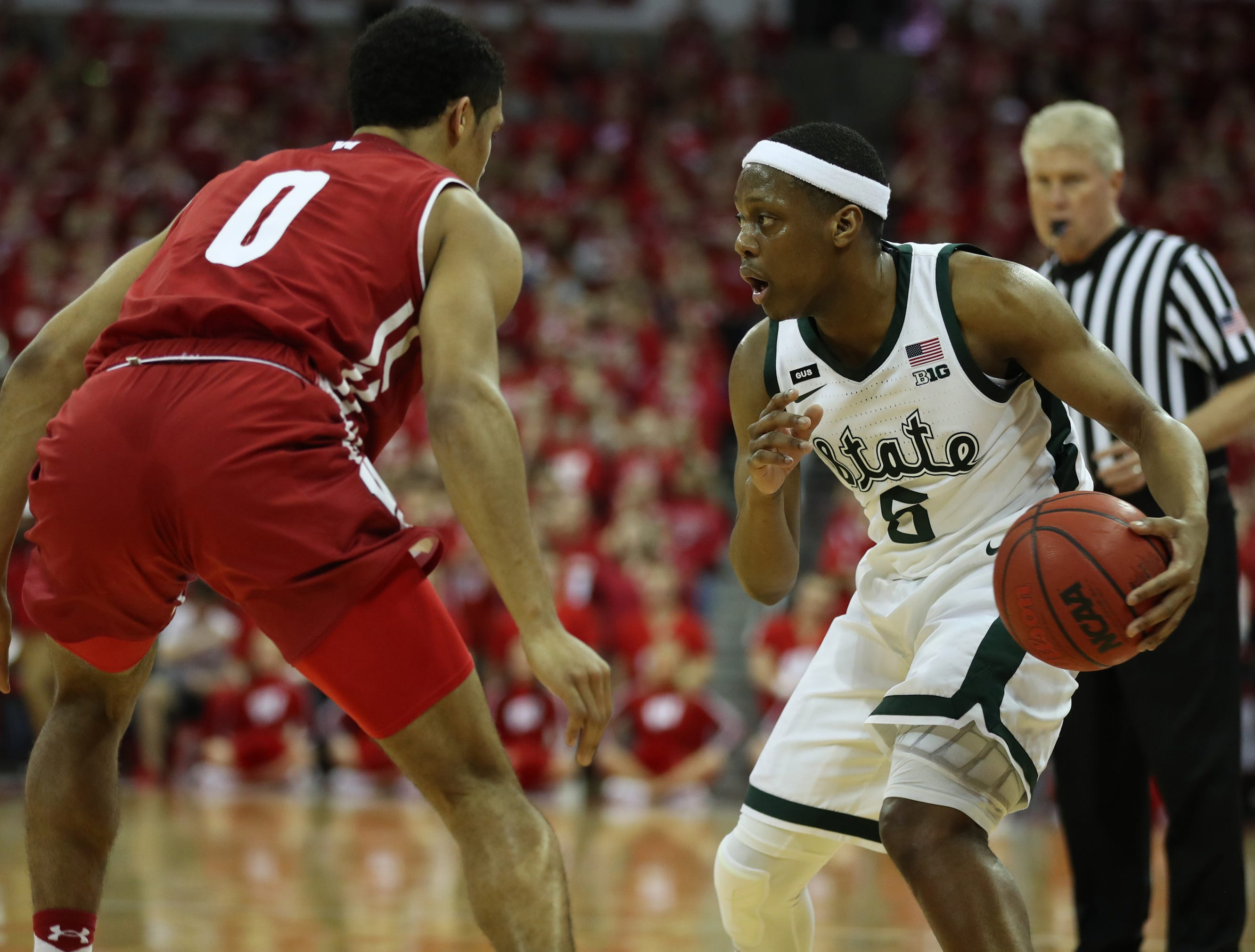 Michigan State Spartans guard Cassius Winston (5) looks to pass as Wisconsin Badgers guard D'Mitrik Trice (0) defends at the Kohl Center