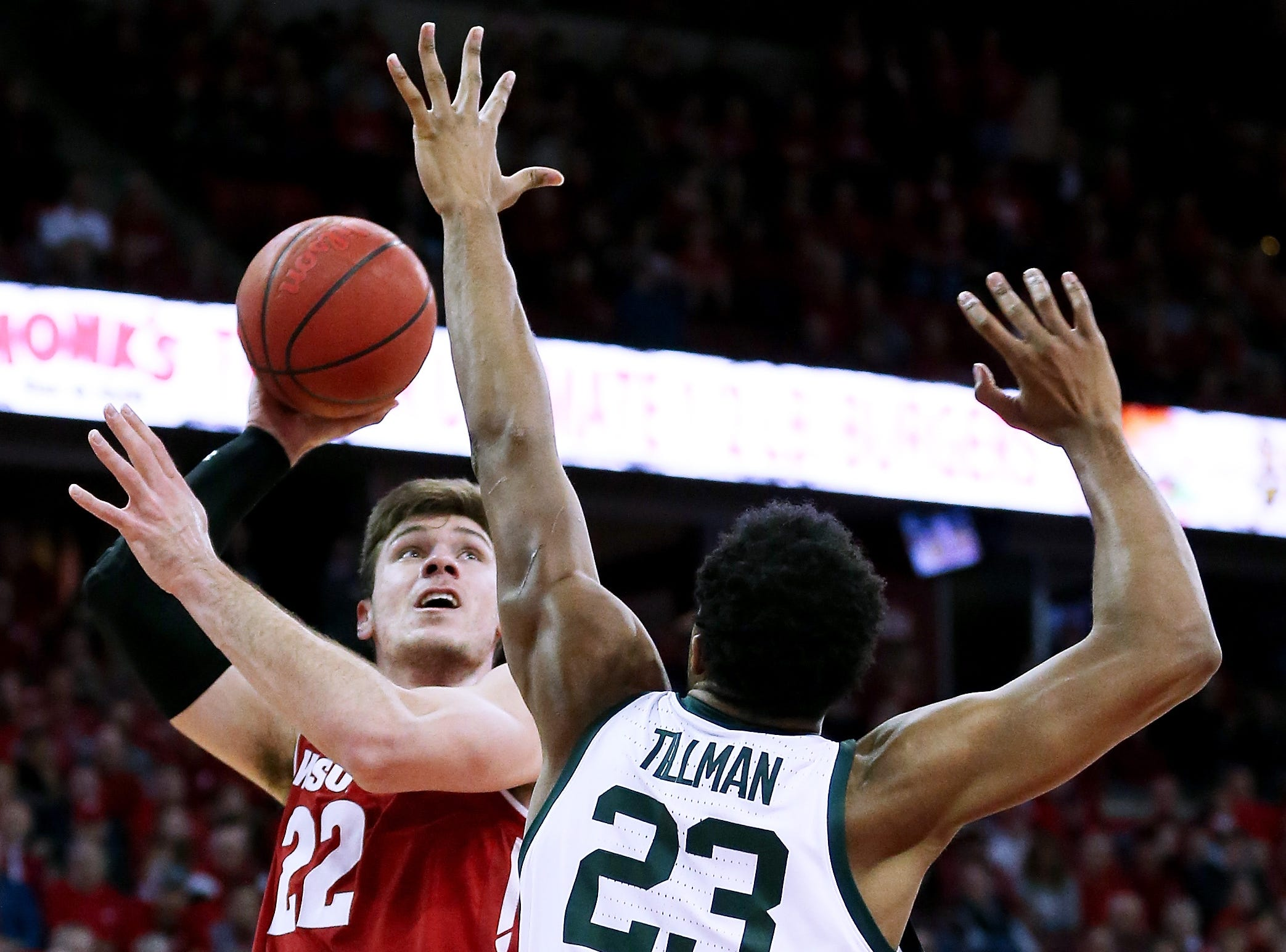 Ethan Happ #22 of the Wisconsin Badgers attempts a shot while being guarded by Xavier Tillman #23 of the Michigan State Spartans in the first half at the Kohl Center on February 12, 2019 in Madison, Wisconsin.