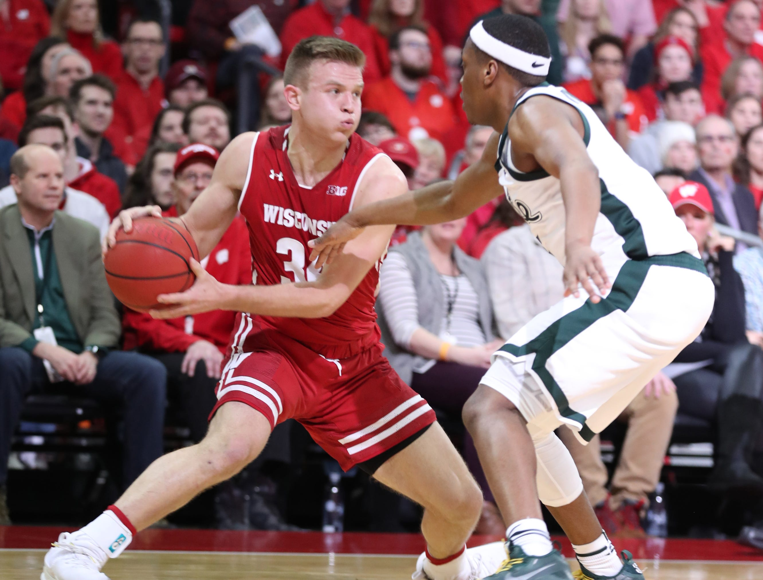 Wisconsin Badgers guard Brad Davison (34) looks to pass the ball as Michigan State Spartans guard Cassius Winston (right) defends during the second half at the Kohl Center.