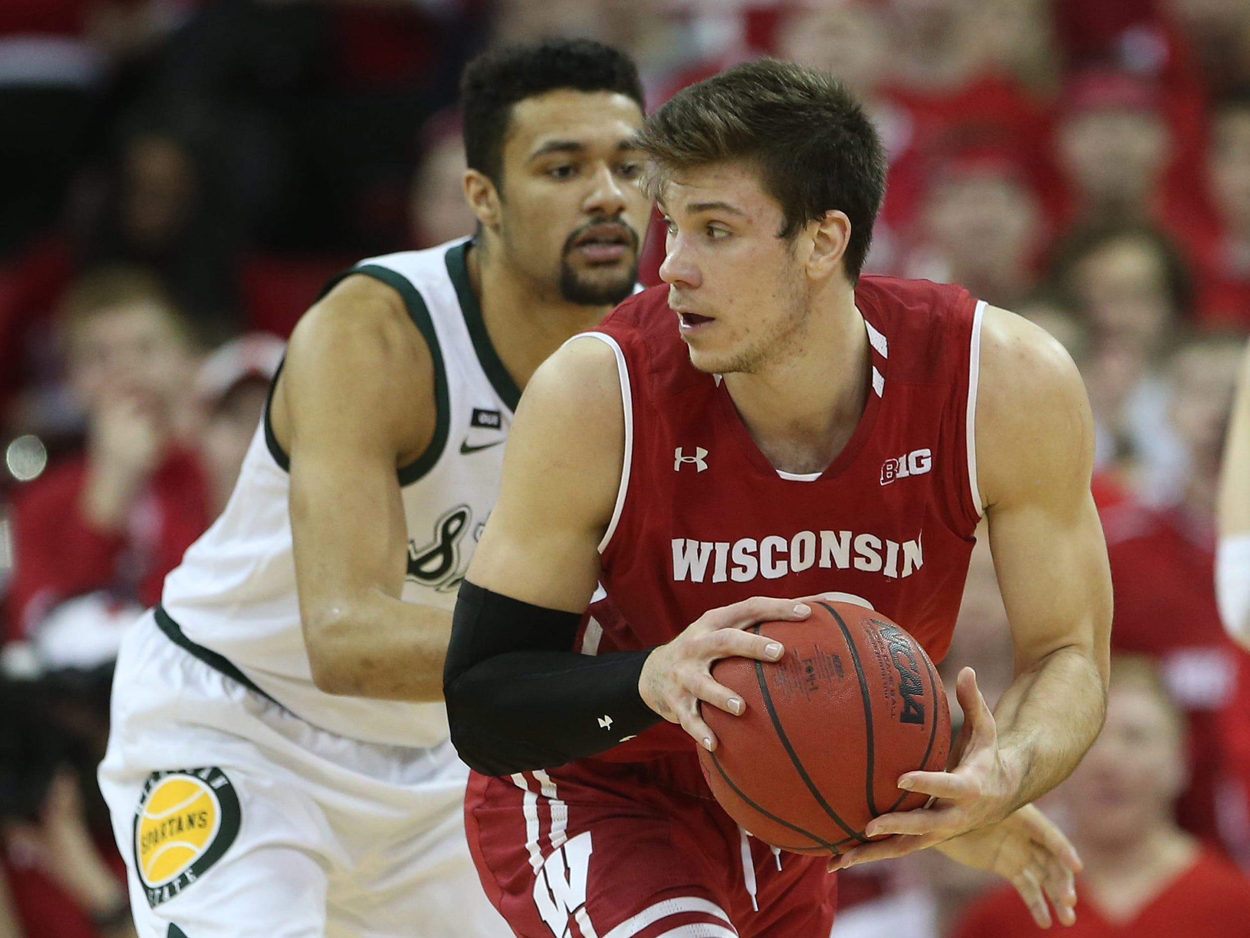 Wisconsin Badgers forward Ethan Happ controls the ball as Michigan State Spartans forward Kenny Goins defends during the first half at the Kohl Center, Feb. 12, 2019.