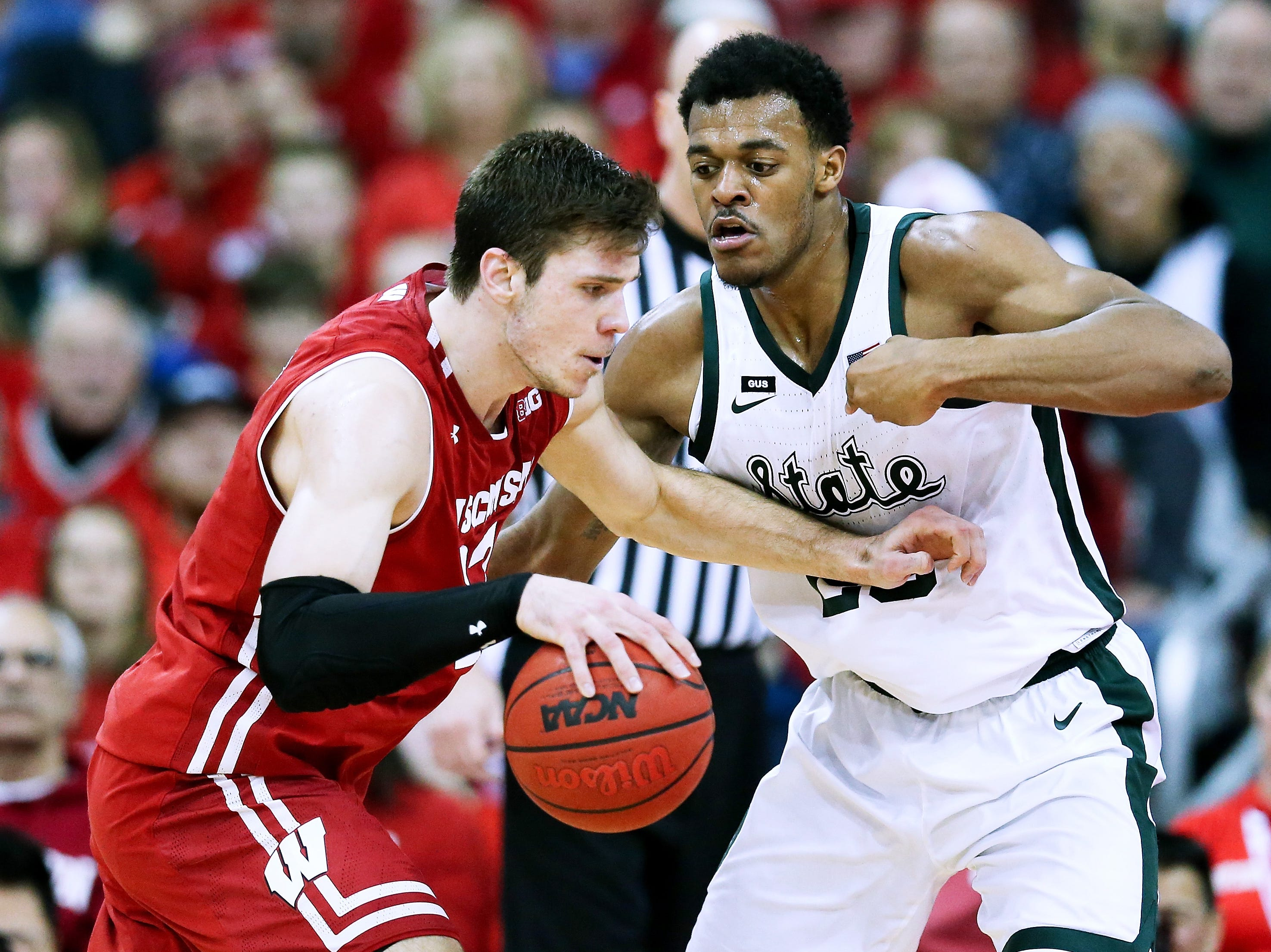 Ethan Happ #22 of the Wisconsin Badgers dribbles the ball while being guarded by Xavier Tillman #23 of the Michigan State Spartans in the second half at the Kohl Center on February 12, 2019 in Madison, Wisconsin.