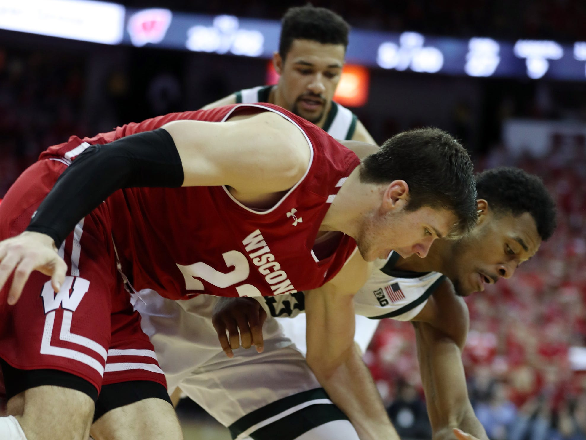 Wisconsin Badgers forward Ethan Happ (22) and Michigan State Spartans forward Kenny Goins (25) battle for a loose ball during the second half at the Kohl Center.