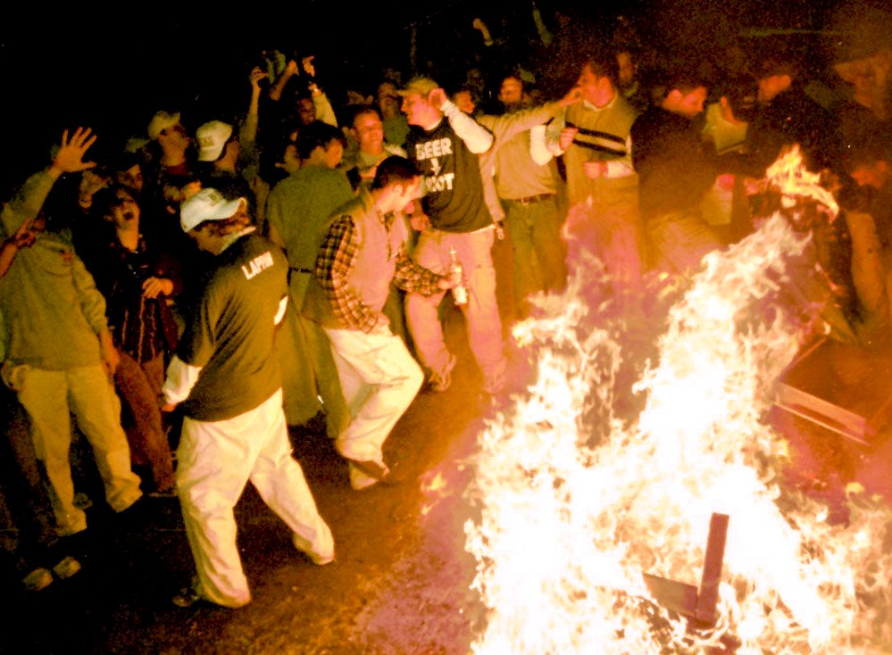 A crowd surrounds a burning couch in the Cedar Village apartment complex in East Lansing after the Michigan State University's loss to Duke in the Final Four of the NCAA Men's Basketball Tournament on Saturday, March 27, 1999.