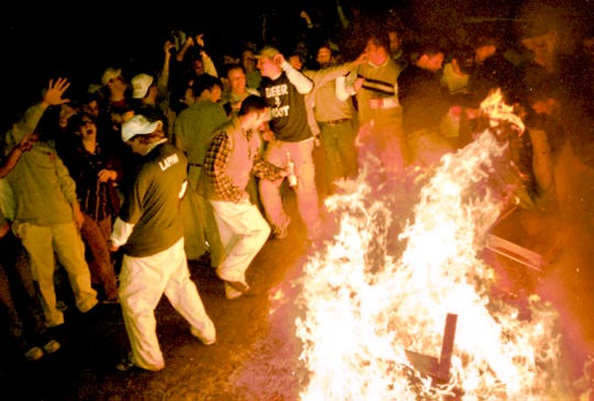 In this 1999 photo, a crowd surrounds a burning couch in the Cedar Village apartment complex in East Lansing after Michigan State lost to Duke in the Final Four of the NCAA Men's Basketball Tournament.