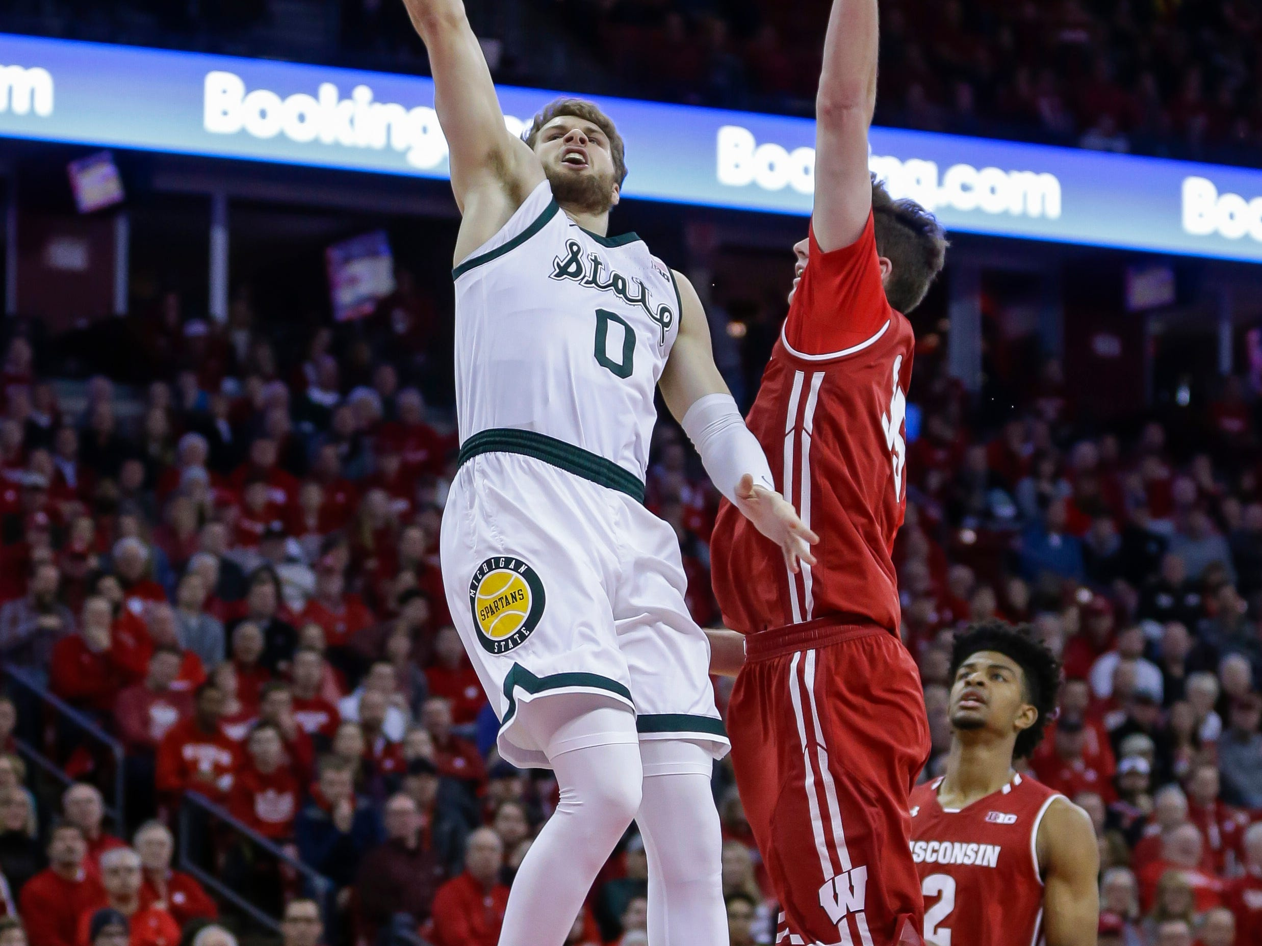 Michigan States's Kyle Ahrens (0) shoots against Wisconsin's Nate Reuvers (35) during the first half of an NCAA college basketball game Tuesday, Feb. 12, 2019, in Madison, Wis.