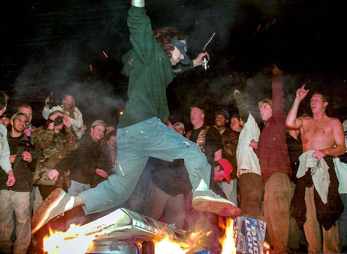 A man jumps over a bonfire in Cedar Village on Saturday, March 27, 1999, in East Lansing.