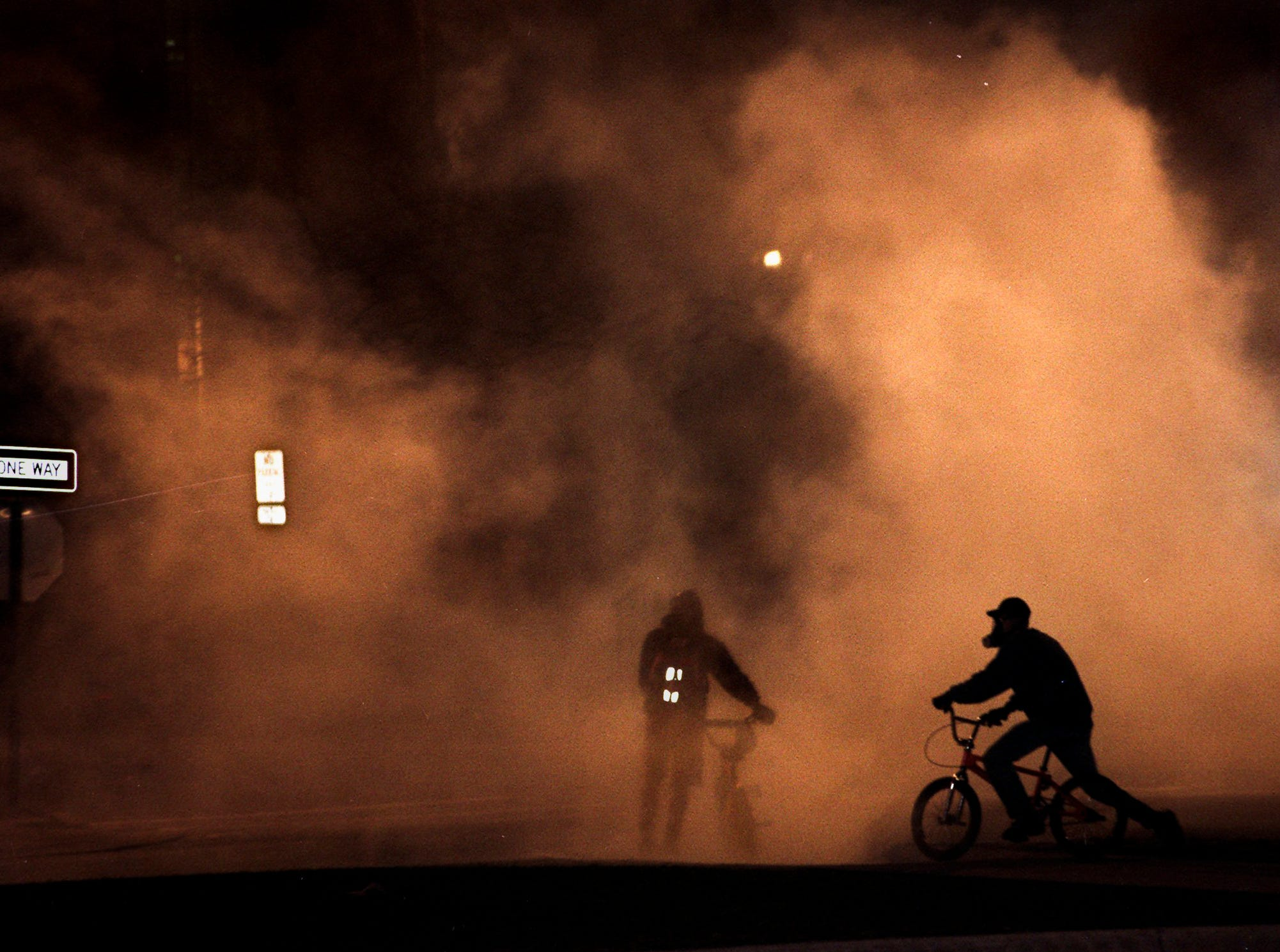 Two men wearing gas masks ride bikes through a cloud of tear gas on Bogue Street during a riot on Saturday, March 27, 1999, in East Lansing.